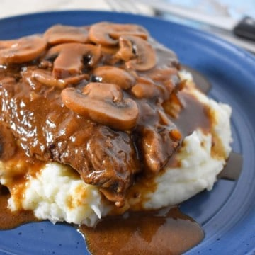 A thick sirloin steak covered in a dark brown mushroom gravy on a bed of mashed potatoes served on a blue plate.
