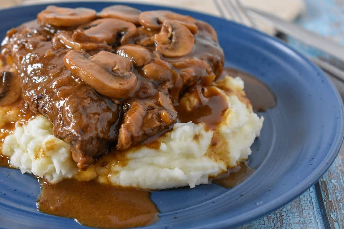 A close up image of the steak with mushrooms on a bed of mashed potatoes served on a blue plate.