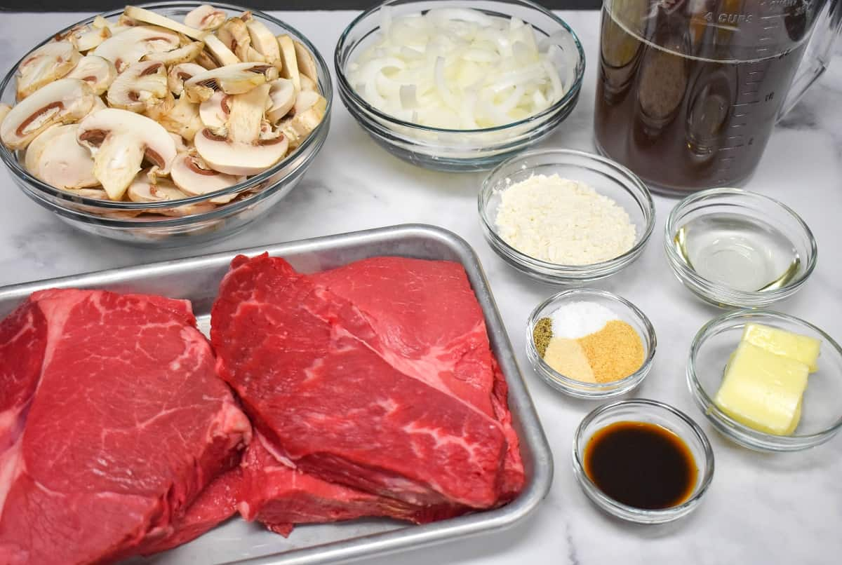 The ingredients for the steak and mushrooms, prepped and arranged on a white table.