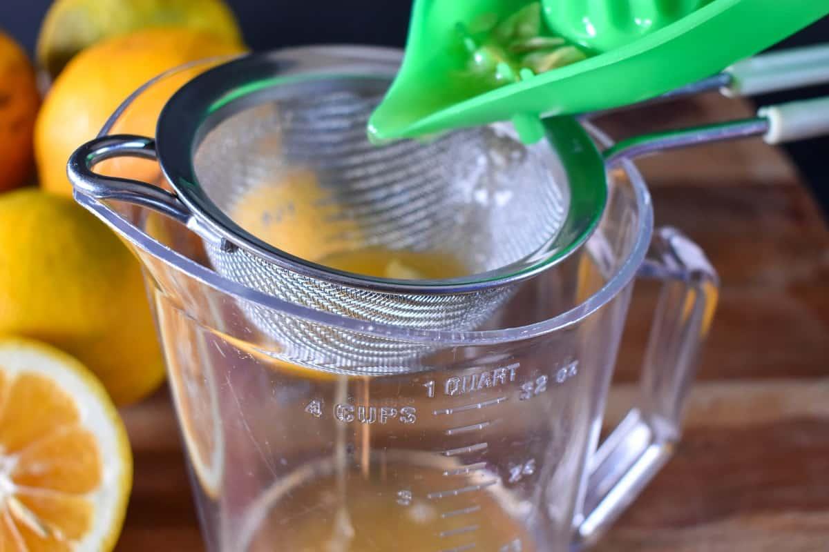 Straining sour orange juice in a mesh strainer.