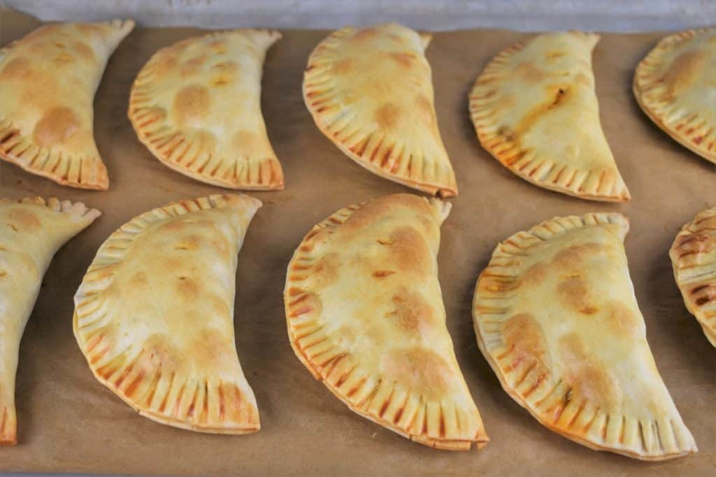 Baked Beef Empanadas arranged on a baking sheet