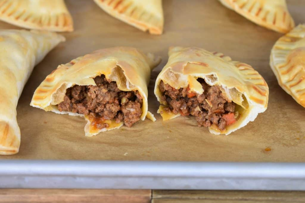 Baked Beef Empanadas on a baking sheet with one cut in half exposing the beef filling