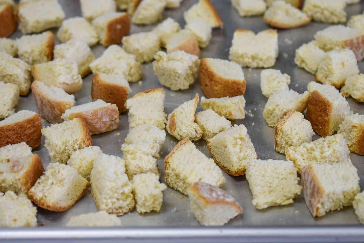 Homemade croutons on a baking sheet.