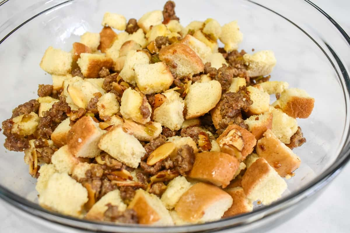 The sausage mixture with the croutons in a large glass bowl set on a white table.