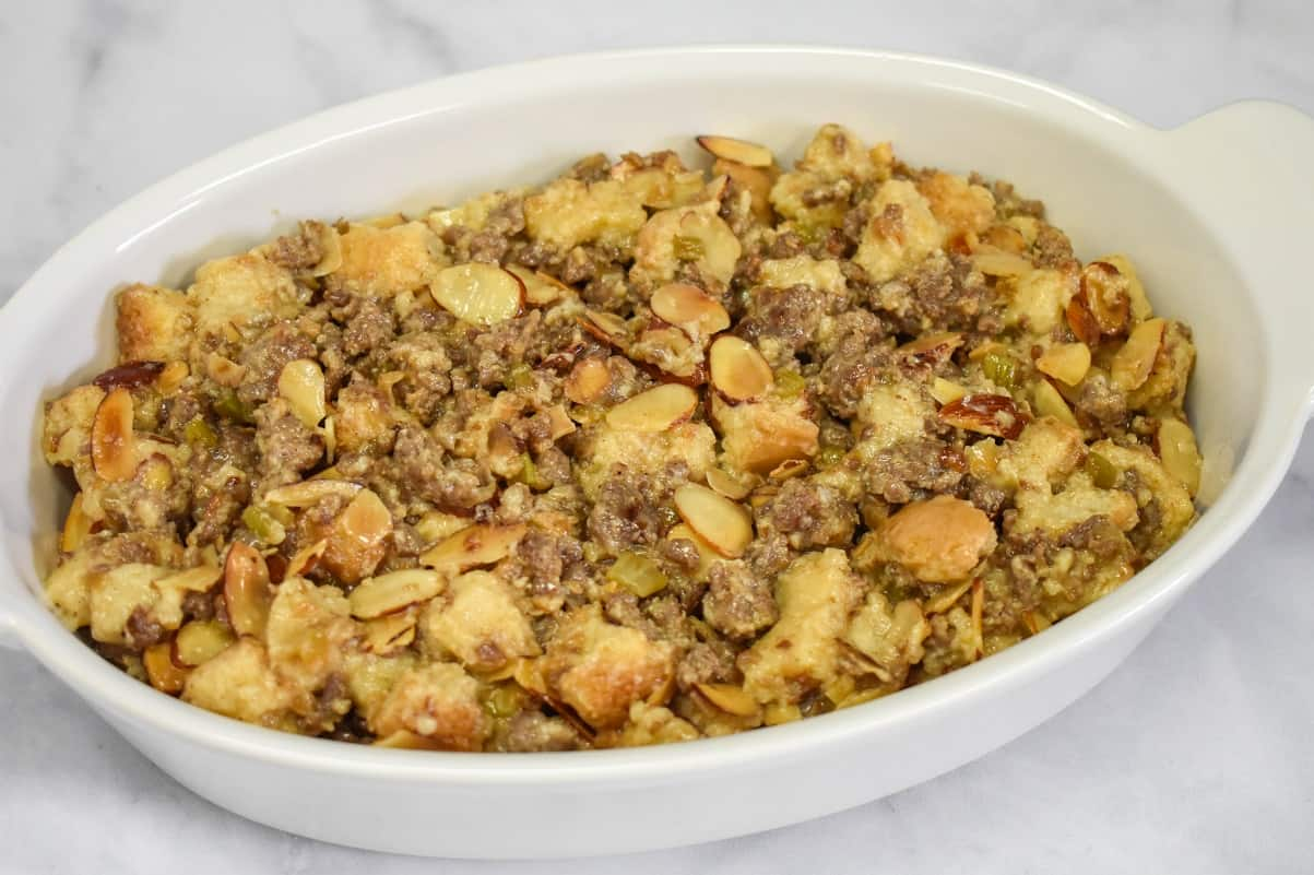 The stuffing in a white casserole dish set on a white table before baking.