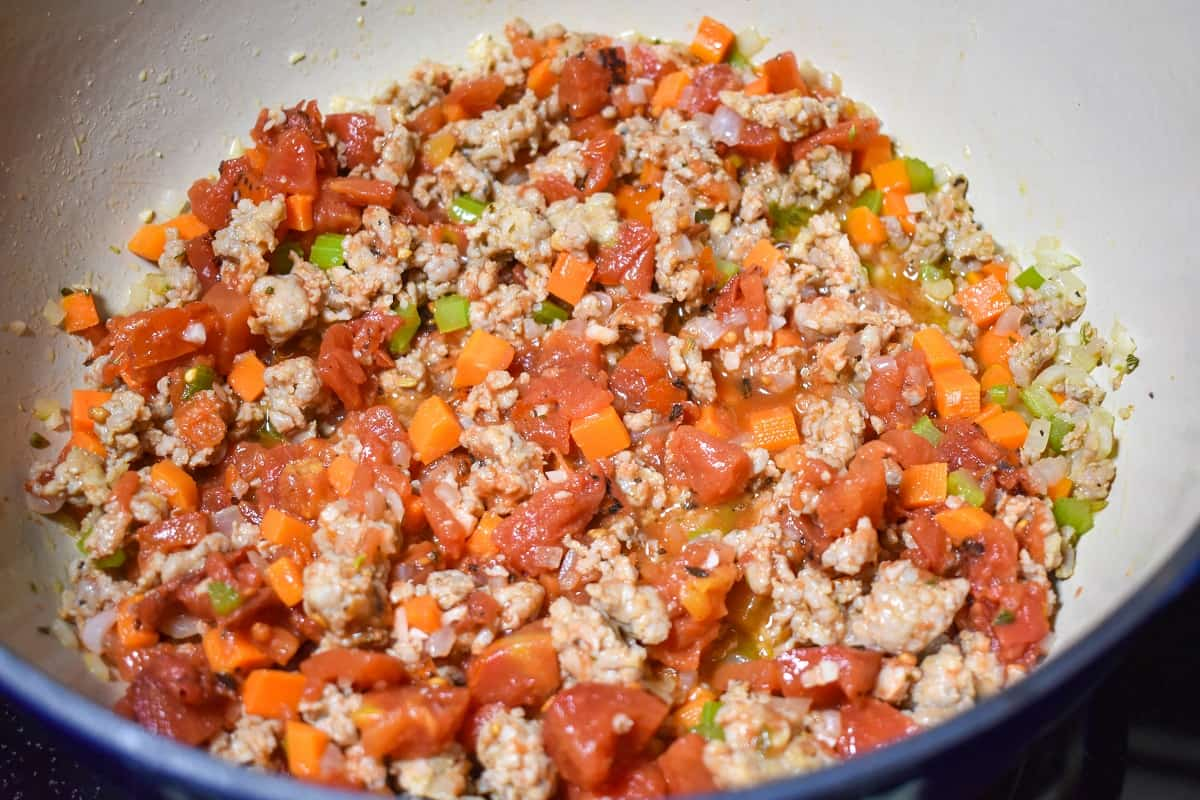 The diced tomatoes stirred in with the sausage and vegetables in a large pot.