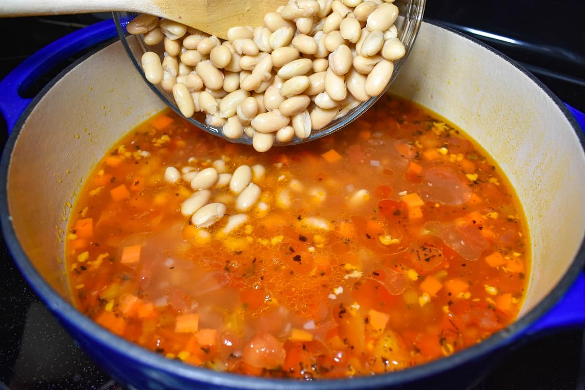 White beans being added to the soup.