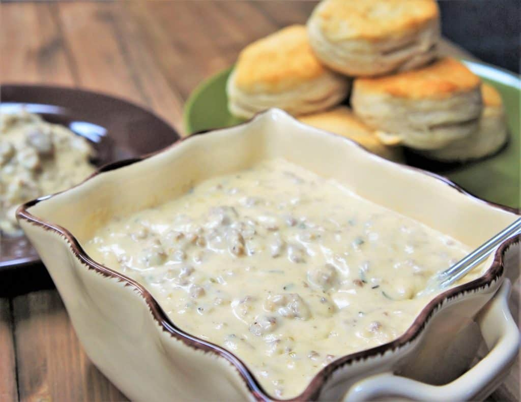 Sausage Gravy served in a light colored bowl with a stack of biscuits in the background.
