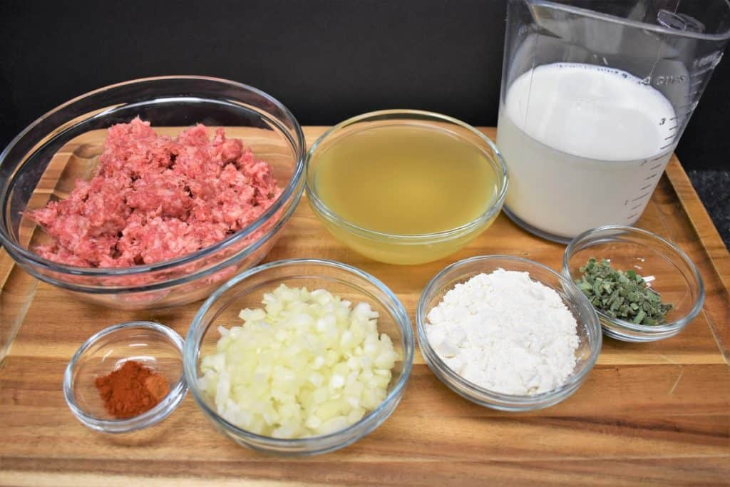 Sausage gravy ingredients in glass bowls displayed on a wood cutting board.