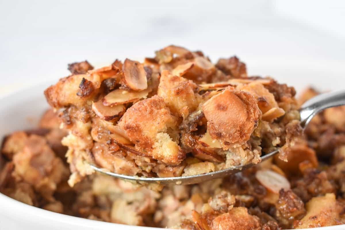 A close up of a serving spoon holding up a serving of the finished stuffing.