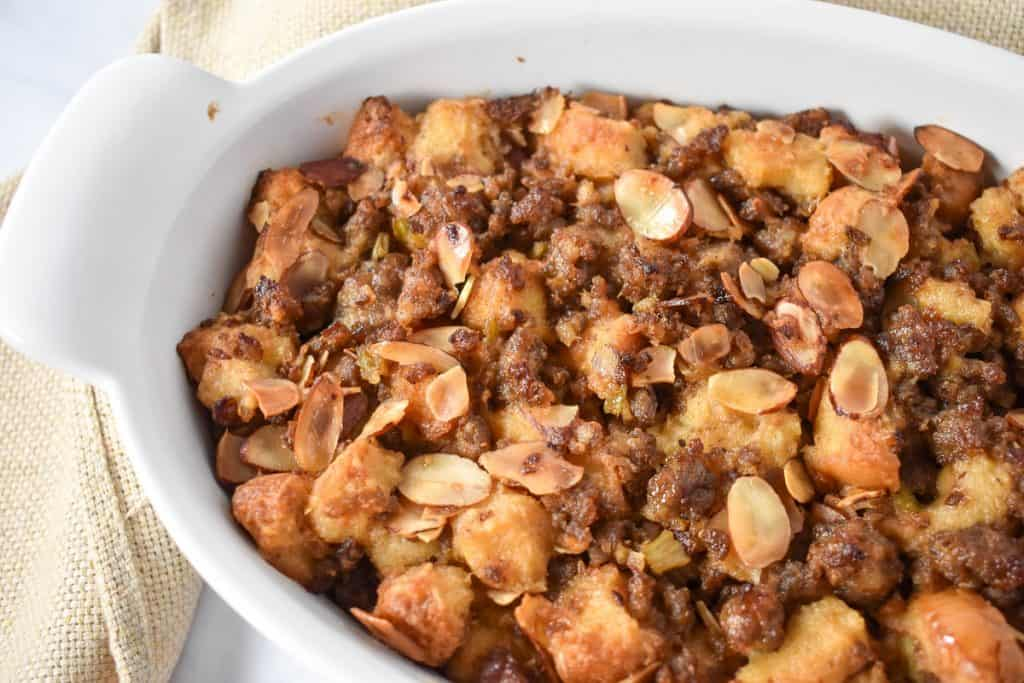 Sausage stuffing in a white casserole dish with a beige linen on the side.