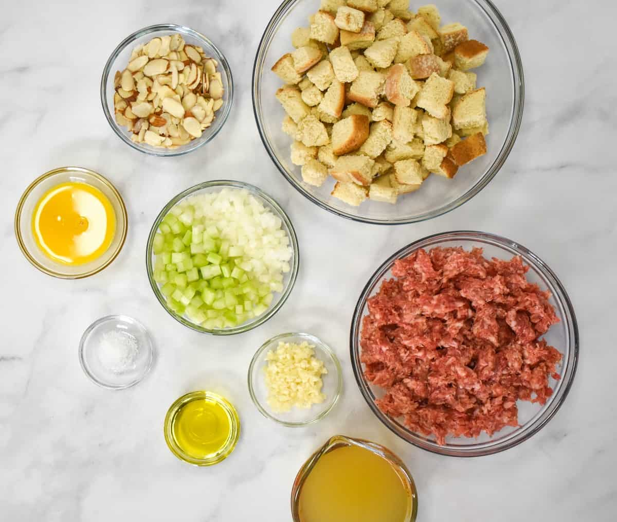 The ingredients for the sausage stuffing, prepped and arranged in glass bowls on a white table.