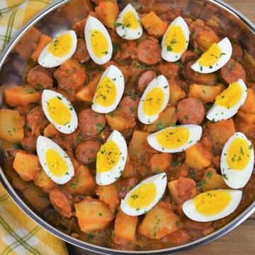 Sausage and Potatoes in a skillet in tomato sauce and topped with quartered hard boiled eggs