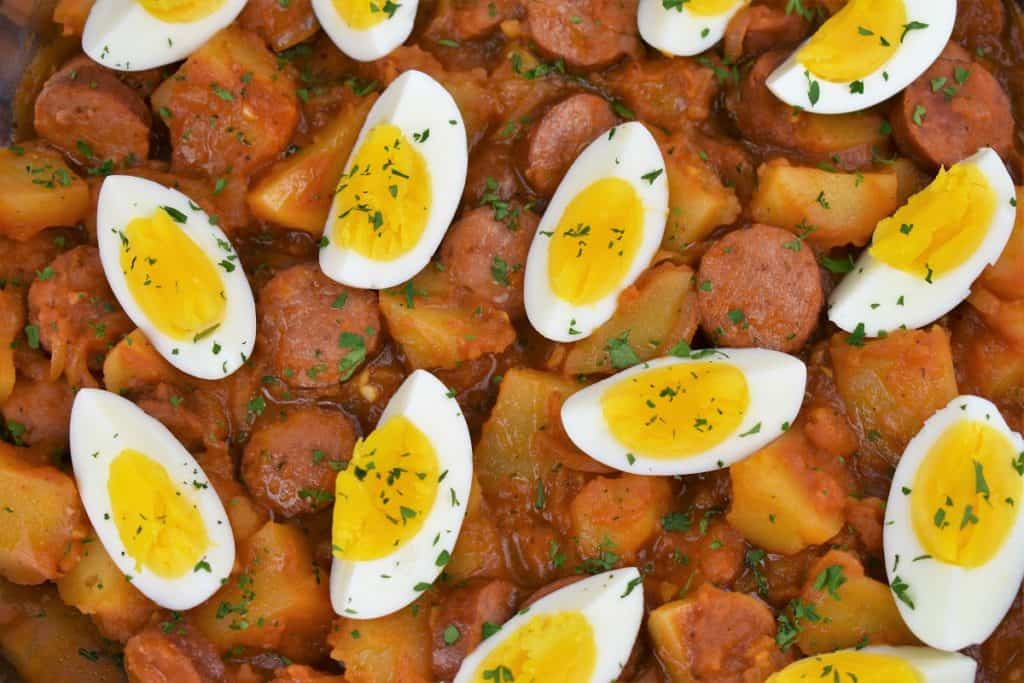 Close up picture of sausage and potatoes topped with quartered hard boiled eggs in a skillet