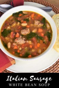 Sausage and White Bean Soup served in a white plate with slices of bread on the side.
