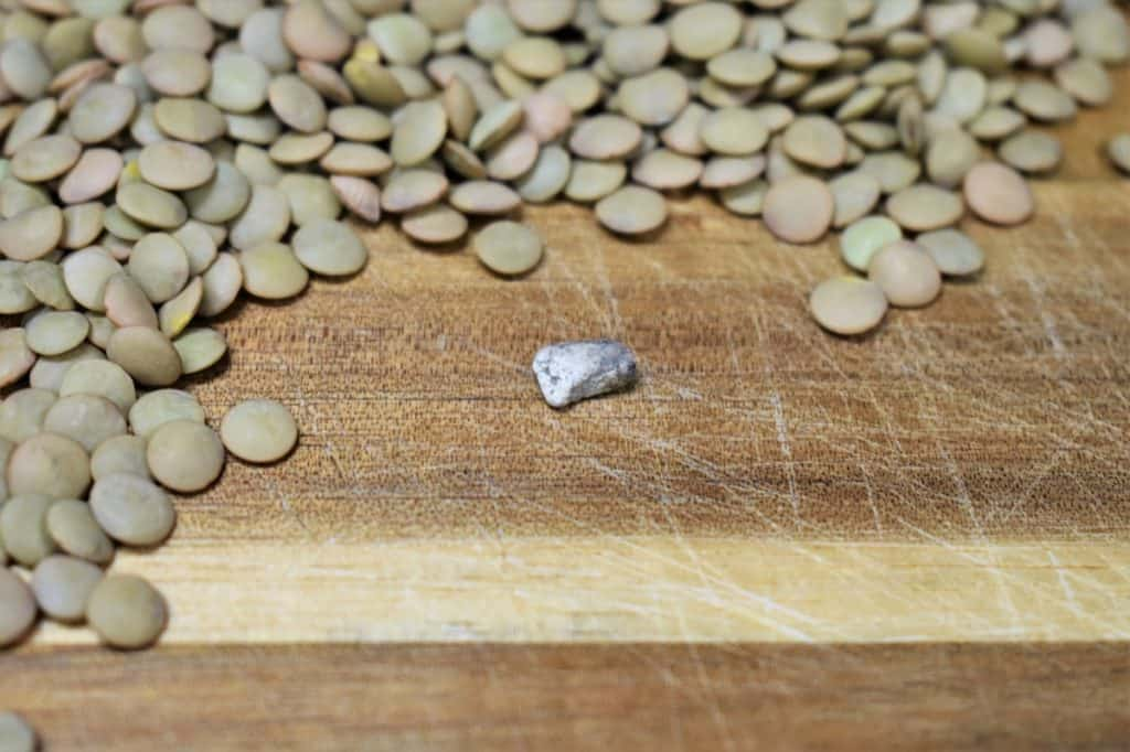 Lentils on a wood cutting board and a small stone that was found in the lentils.