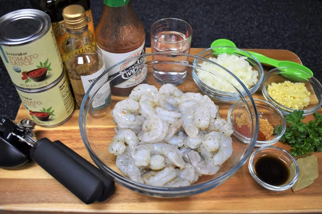 Camarones Enchilados Prep Work, raw shrimp, spices, sauces, diced onions and garlic displayed on a wood board