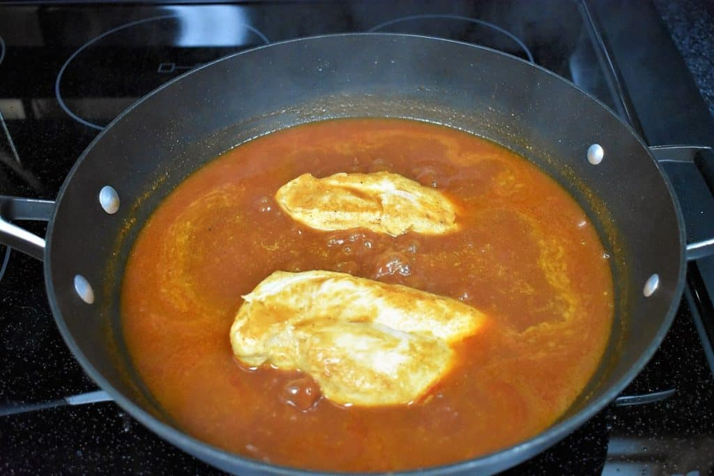 Two chicken breasts being cooked in a red enchilada sauce in a large black skillet.