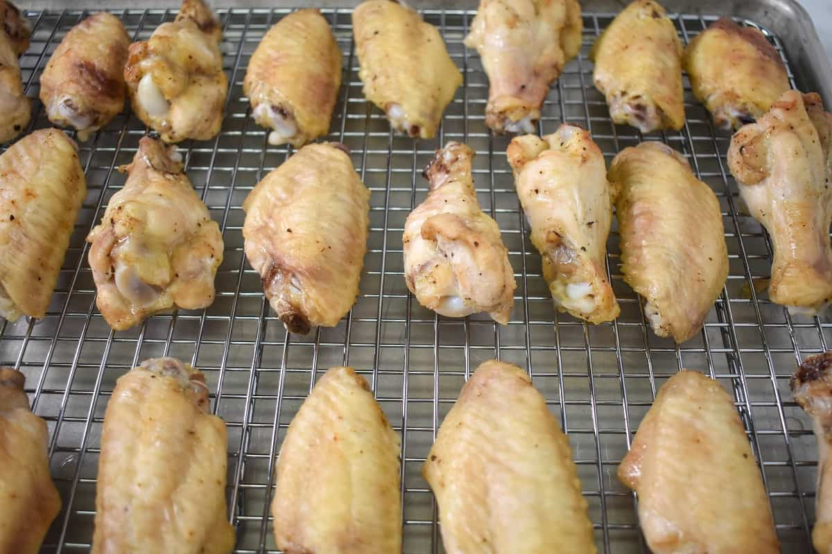 The half-baked wings arranged on a large baking sheet that's lined with a cooling rack.