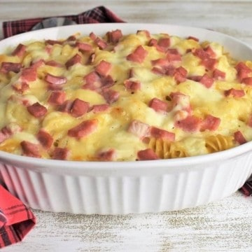 Baked ham and cheese pasta in a large white casserole dish