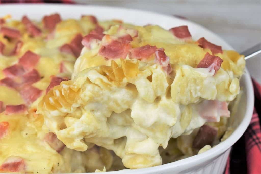 Baked ham and cheese pasta in a large white casserole dish being lifted with a serving spoon