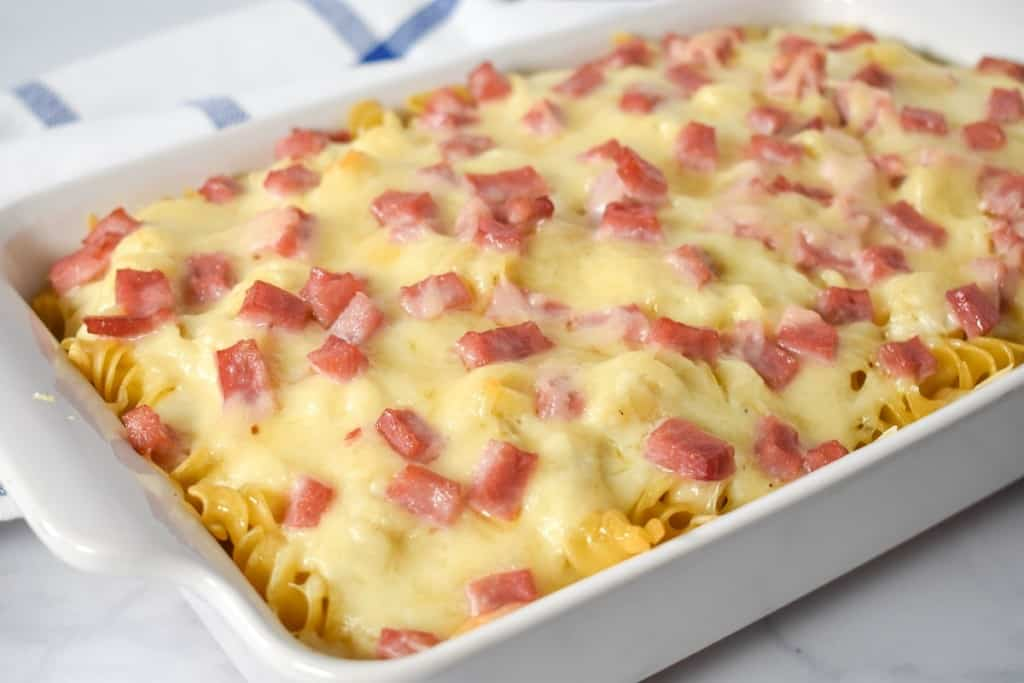 The finished ham and cheese casserole displayed on a table with a blue and white linen in the background.