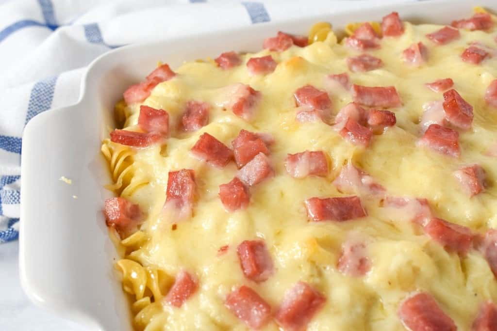 A close up of the ham and cheese casserole in a white casserole dish.