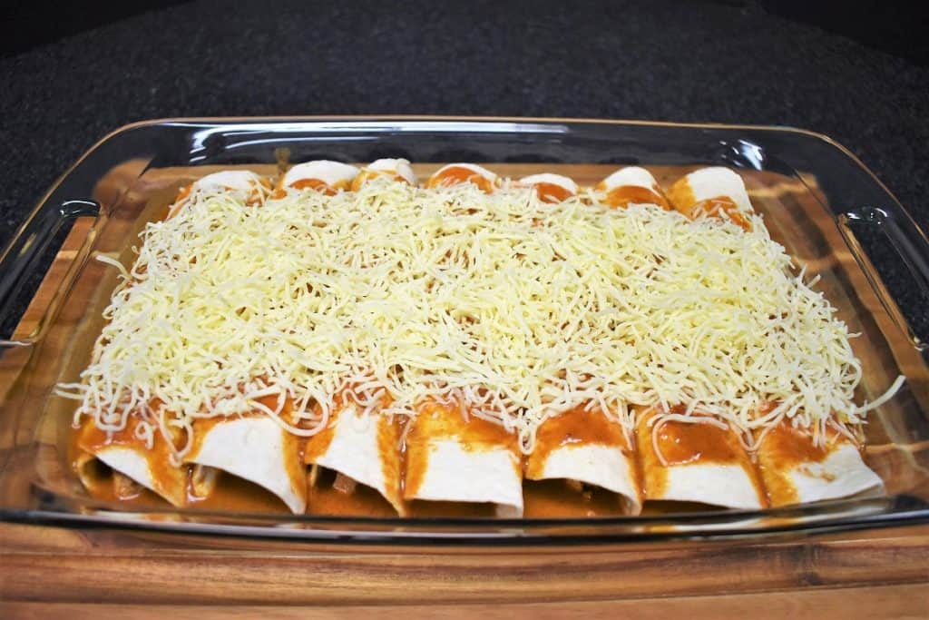 Chicken enchiladas arranged in a casserole dish, prior to baking, topped with the enchilada sauce and shredded cheese