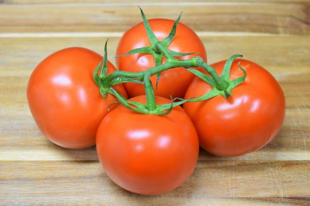 Four Medium Vine Ripe Tomatoes on a wood cutting board