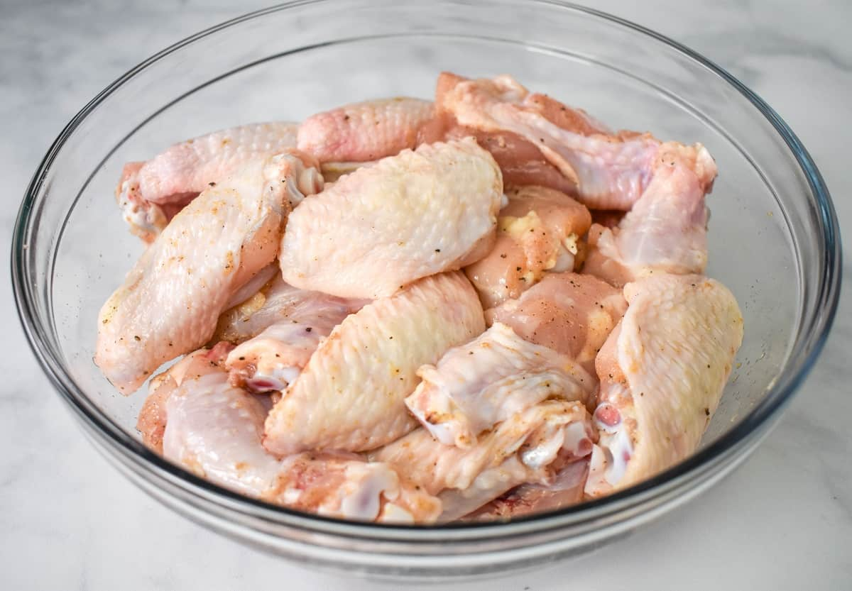 The seasoned wings in a large clear bowl.
