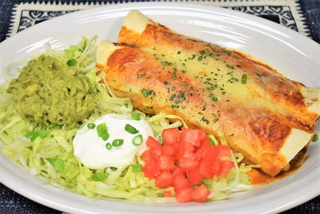 Shredded Chicken Enchiladas served on a large white platter with shredded lettuce, guacamole, sour cream and diced tomatoes