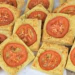 Tomato Bread puff pastry cut into squares with a thin slice of tomato in the center