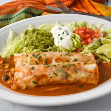 An image of the chicken enchiladas served on a large white plate with lettuce, guacamole, sour cream and tomatoes. In the background there is a linen with red, orange and green lines.