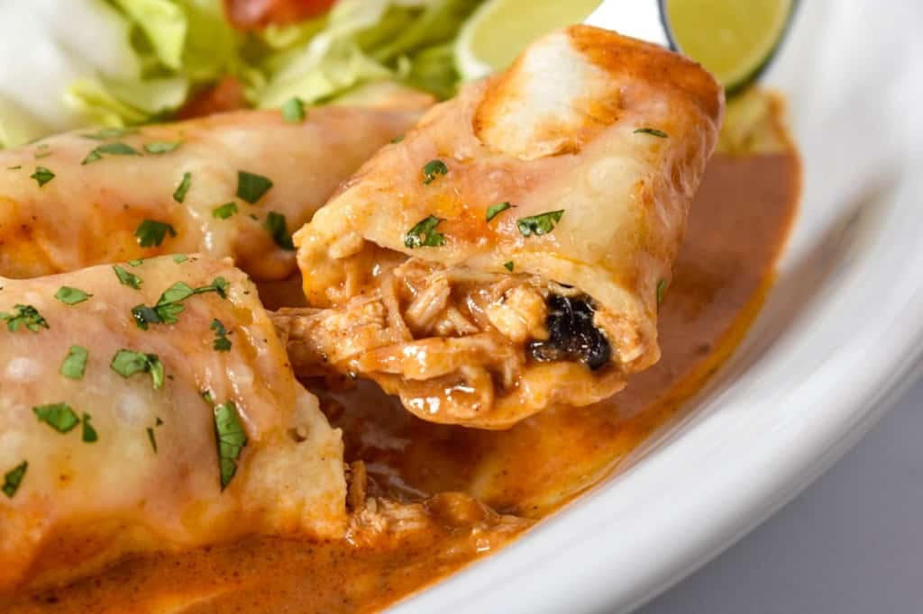 A close up image of a piece of the enchilada cut so that the inside is visible, served on a white plate.