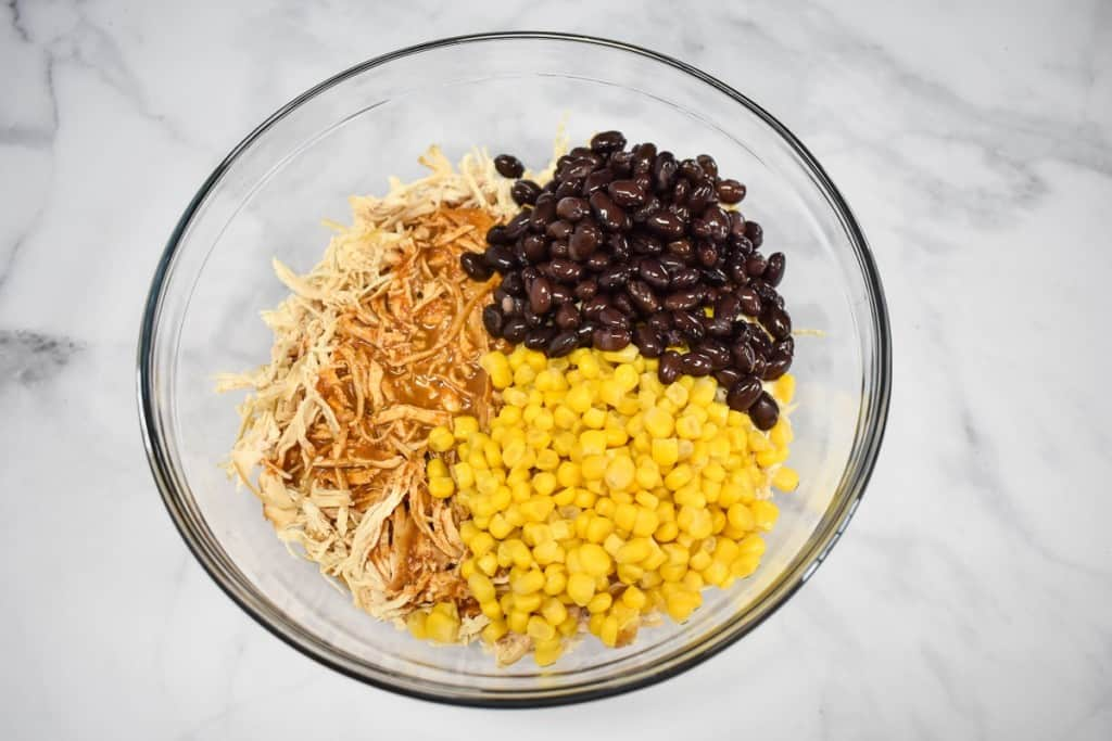 An image of shredded chicken, black beans and corn in a large glass bowl set on a white table.