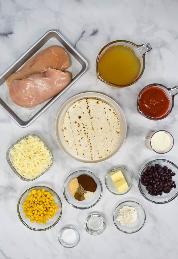 The ingredients for the recipe prepped and arranged in separate glass bowls arranged on a white table.