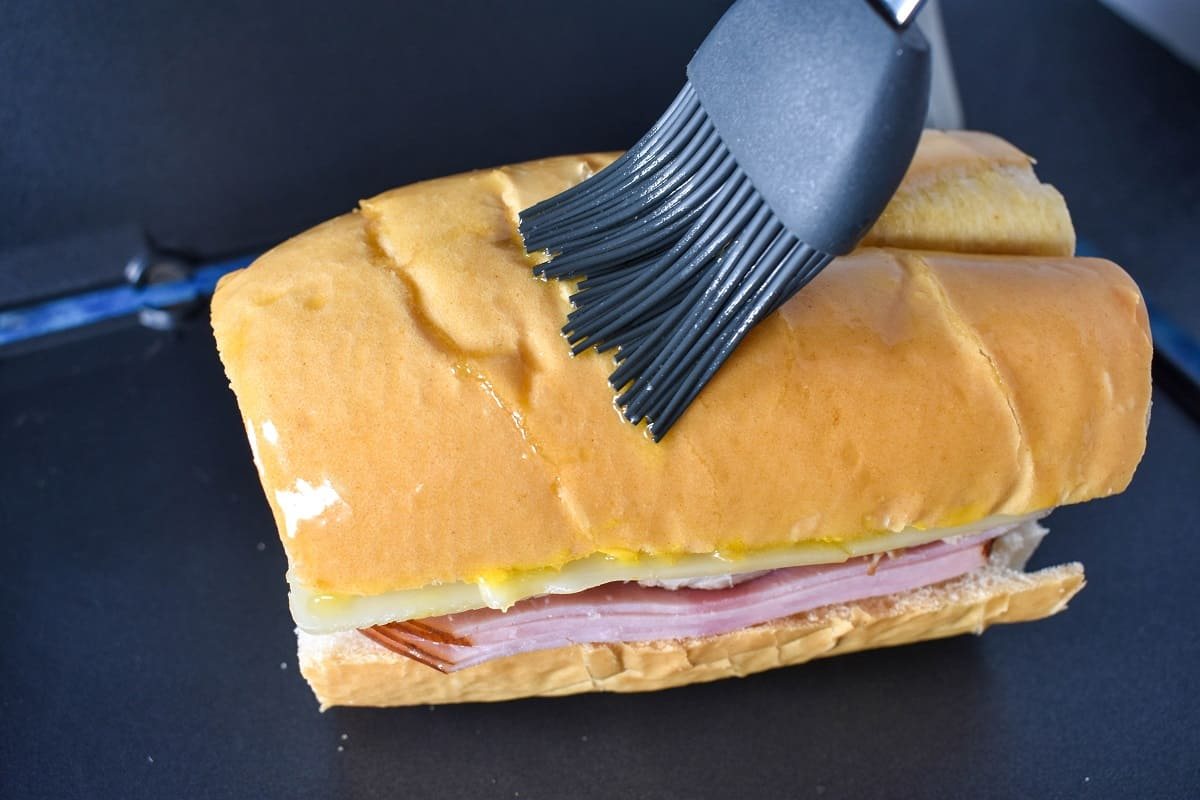 A gray silicone brush applying butter on the top slice of cuban bread.