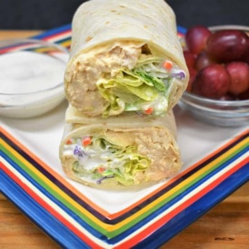 Buffalo Chicken Wrap cut in half and stacked served with ranch dressing and grapes on the side