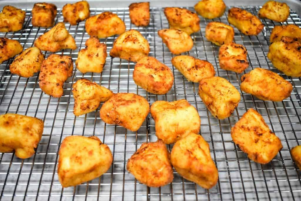 Cooked golden browned chicken nuggets arranged on a cooling rack.