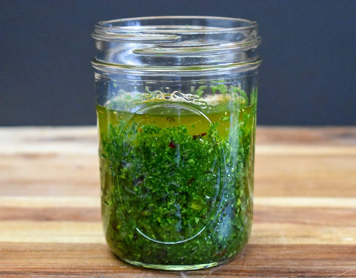 Chimichurri sauce in a clear glass canning jar displayed on a wood cutting board.