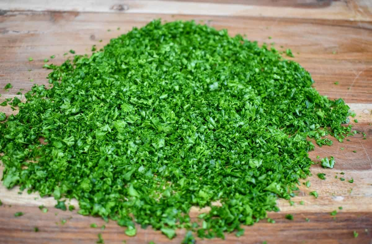Finely chopped parsley on a wood cutting board.