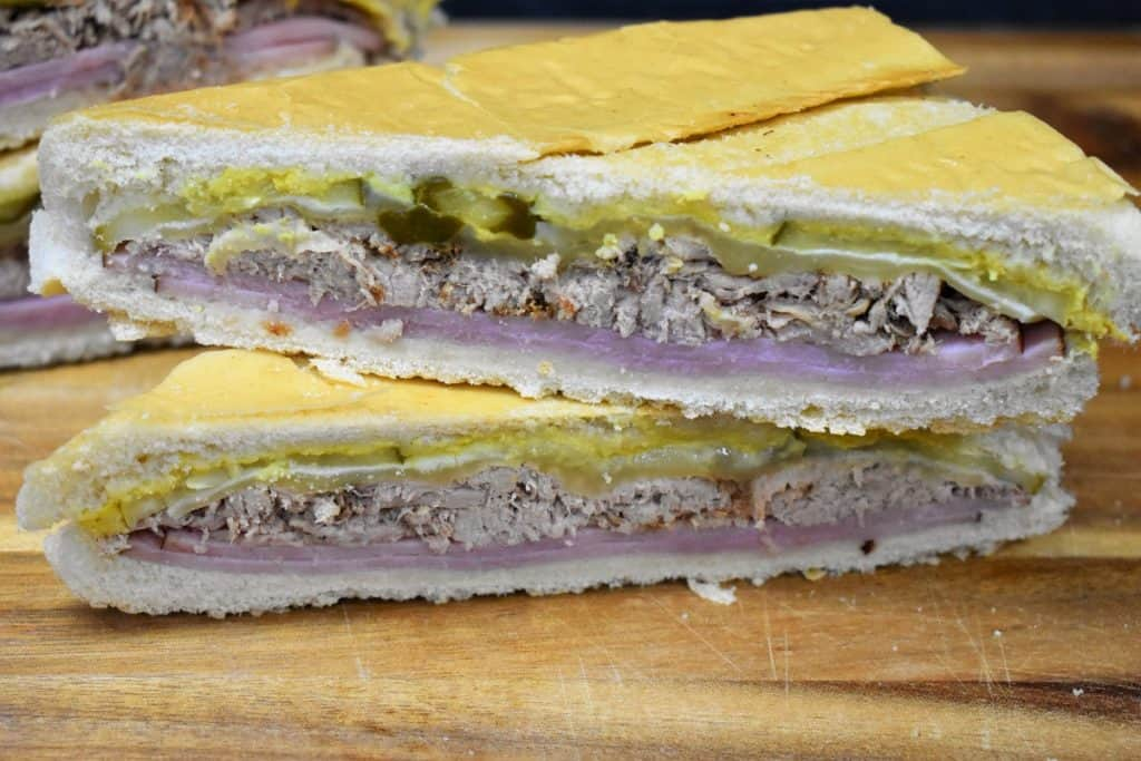 Cuban Sandwich cut in half and stacked one on top of the other
