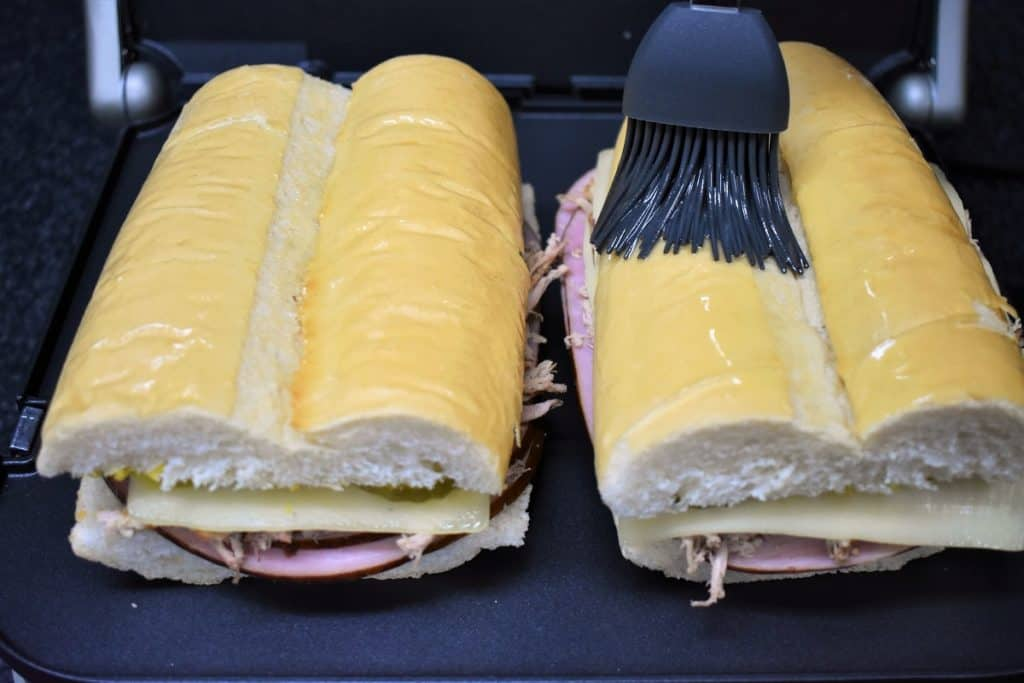 Cuban Sandwich being brushed with butter on the top