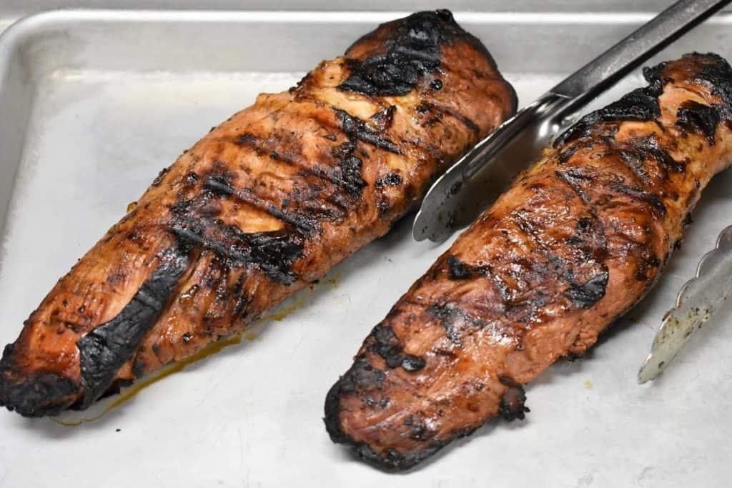 Two grilled pork tenderloins on a metal pan