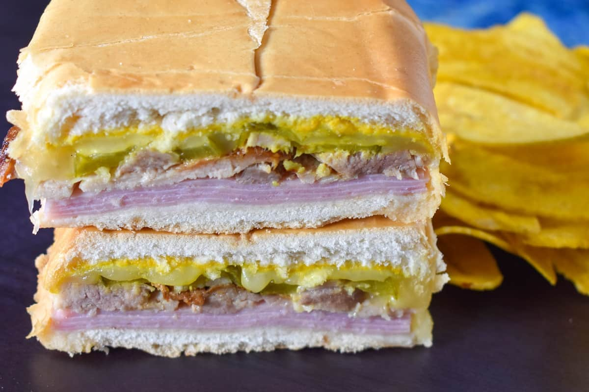 A close up image of the cuban sandwich displayed on a black surface with yellow plantain chips on the right hand side.