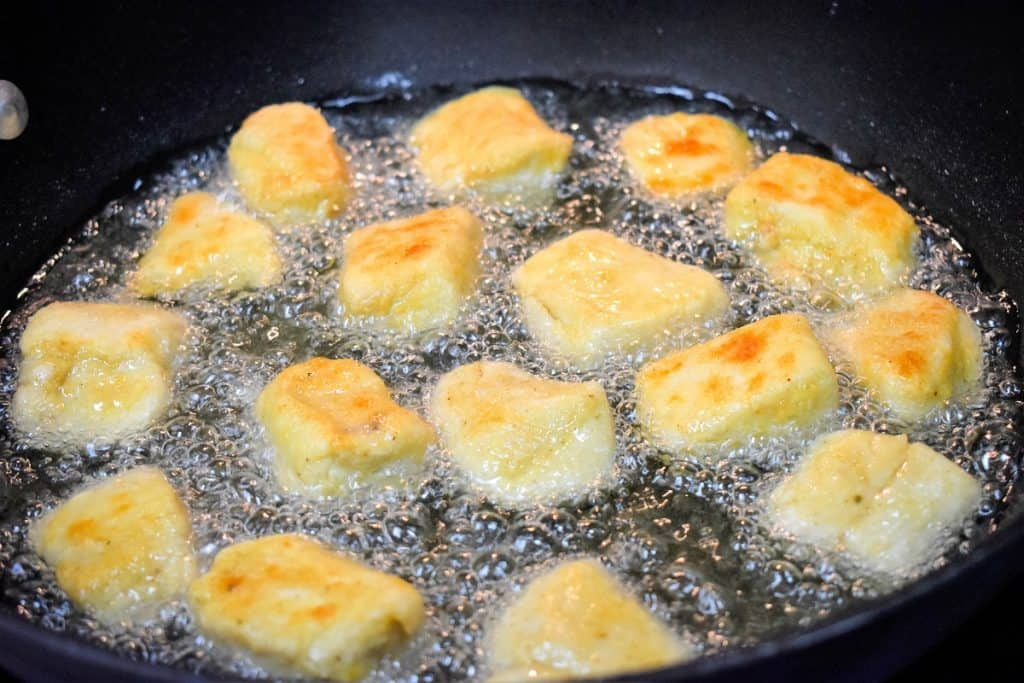 Chicken nuggets sizzling in oil in a large, black skillet.