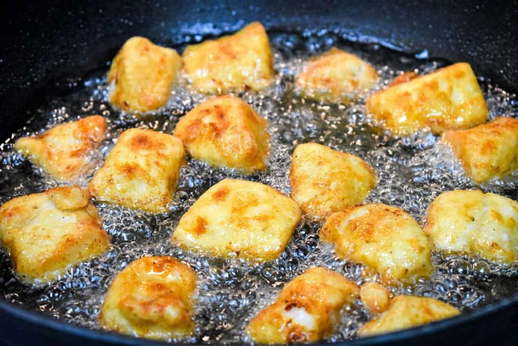 Chicken nuggets that are golden browned, sizzling in oil in a large, black skillet.