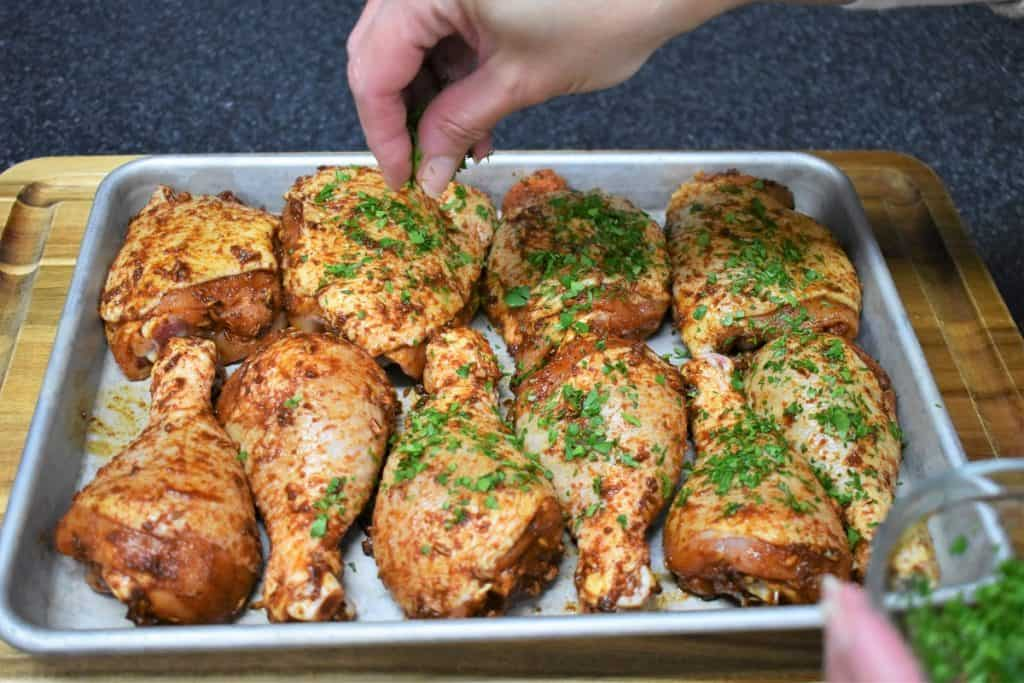 Seasoned Spicy Baked Chicken on a baking sheet being sprinkled with chopped parsley.