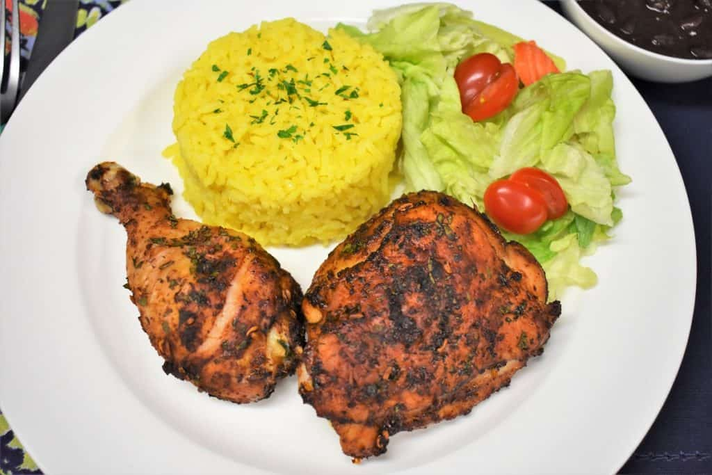A cooked spicy baked chicken thigh and drum on a white plate with a side salad and yellow rice.