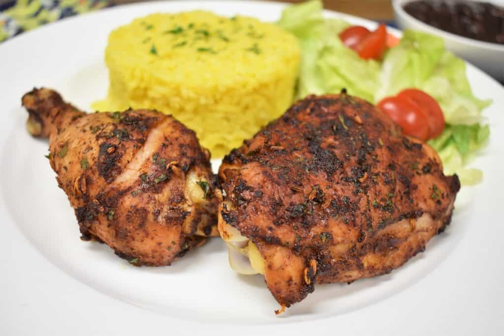 Spicy Baked Chicken, thigh and drum on a white plate with a side salad and yellow rice